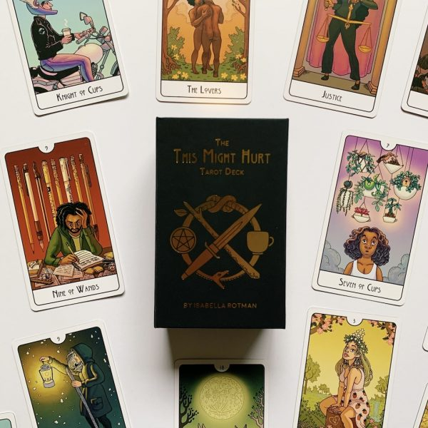 Cards and the box from the This Might Hurt Tarot laid out on a white background