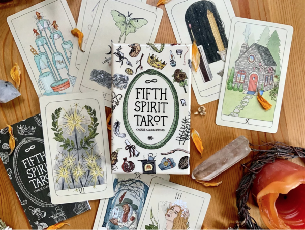 The Fifth Spirit Tarot, on a table with cards and a candle