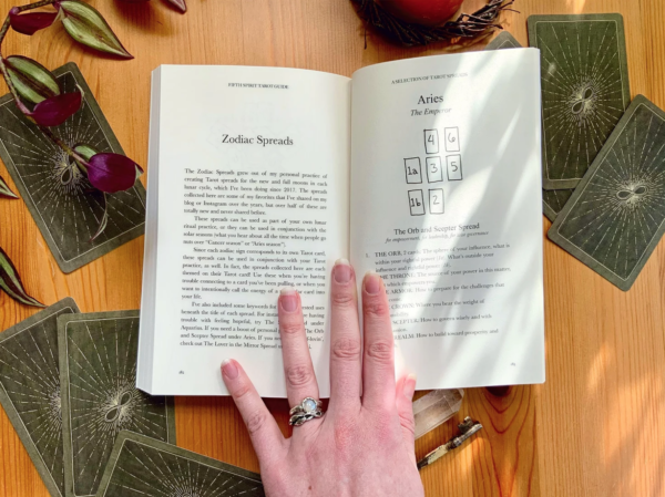 The Fifth Spirit Tarot Guide held open to show pages with a tarot spread